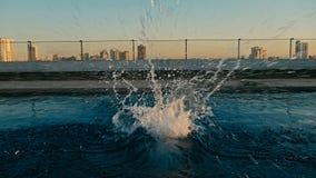 水飞溅在某人以后的跳跃了到水在日落在屋顶水池 库存图片