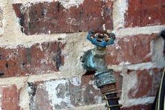 水龙头把柄和水管在边在房子 库存照片