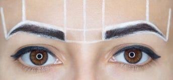 永久补偿美丽的妇女眼眉有厚实的眉头的在美容院 免版税库存图片