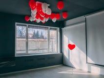 永远沿在othe气球下站立红色心脏形状气球在办公室 是特别华伦泰概念 免版税库存照片