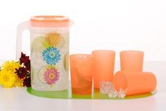 汁液和四个塑料杯子的投手 库存照片