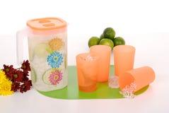 汁液和四个塑料杯子的投手 免版税库存照片