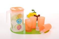 汁液和四个塑料杯子的投手 免版税库存图片