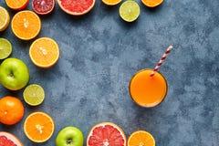 汁液或圆滑的人用柑桔,苹果,葡萄柚在蓝色背景 顶视图,选择聚焦 戒毒所,节食 免版税图库摄影