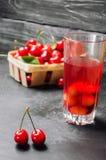 汁液或蜜饯用樱桃 在一个篮子的新鲜的成熟红色樱桃在灰色具体背景,夏天莓果,夏天饮料 免版税库存图片