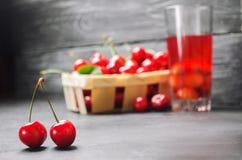 汁液或蜜饯用樱桃 在一个篮子的新鲜的成熟红色樱桃在灰色具体背景,夏天莓果,夏天饮料 免版税库存照片
