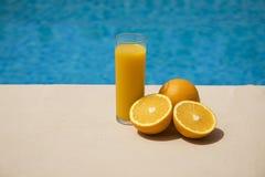 汁液桔子游泳池边 库存照片