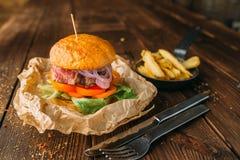 汁液汉堡用在木桌特写镜头的牛排 库存图片