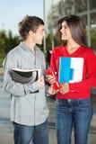 给汁液瓶的学生在校园里的朋友 免版税库存照片