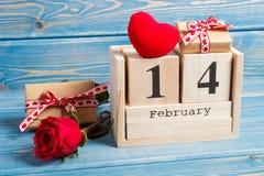 求与日期2月14日,礼物、红色心脏和玫瑰色花,情人节装饰的日历的立方 免版税库存照片