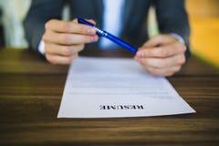 求职者回顾他的在他的书桌上的履历在找到与笔的新的工作的送前 免版税库存照片