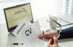 求职者在家庭办公室 有动机的申请人 现代求职,寻找和就业 读他的cv或履历的人 库存图片