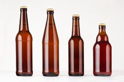 汇集不同的棕色啤酒瓶,大模型 做广告的,设计,在白色木桌上的品牌身份模板 图库摄影