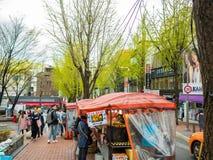 汉城,韩国- 2018年4月14日:在一个街道食物摊位的人买的食物在2018年4月14日的Hongdae街道, 这个区域我 免版税库存图片