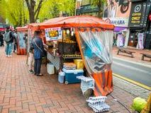 汉城,韩国- 2018年4月14日:在一个街道食物摊位的人买的食物在2018年4月14日的Hongdae街道, 这个区域我 图库摄影