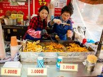 汉城,韩国- 2018年4月14日:在一个街道食物摊位的人买的食物在2018年4月14日的Hongdae街道, 这个区域我 免版税图库摄影