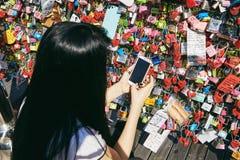 汉城,韩国- 2014年10月8日:女孩作为射击了爱钥匙在锁以后到位在Namsan塔 免版税库存图片