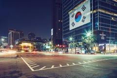 汉城,韩国- 2015年8月16日:汉城大城市政府射击香港大会堂大厦在与韩国旗子的晚上看见 图库摄影