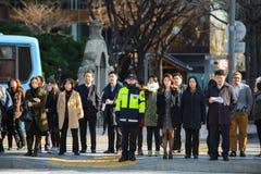 汉城,韩国- 2015年12月16日:等待未认出的步行者穿过路在Gwanghwamun广场 图库摄影