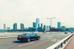 汉城,韩国- 2015年8月14日:通过横跨汉江的汽车桥梁有在背景-汉城,韩国的企业大厦的 免版税库存图片