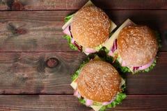 汉堡三明治用香肠、乳酪和菜在木背景 库存照片