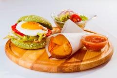 汉堡包三明治、油煎的土豆和鸡蛋,沙拉,调味汁,在餐馆,白色背景,食物菜单照片服务 免版税库存图片