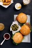汉堡包和乳酪汉堡黑暗的表面上用贮藏啤酒和油炸物 库存图片