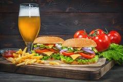 汉堡包和低度黄啤酒在客栈背景 免版税库存照片