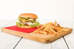 汉堡包和炸薯条在木桌上 免版税库存照片