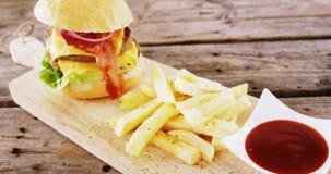 汉堡包和炸薯条用西红柿酱在砧板保持了 股票视频