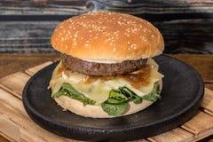 汉堡包用乳酪和番茄酱在黑木板材 库存图片
