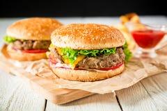 汉堡包用牛肉、调味汁和炸薯条在木桌上 顶视图 美国鲜美食物 库存图片