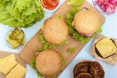 汉堡包用水多的炸肉排、蕃茄、泡菜和黄瓜、乳酪、绿色莴苣叶子和一个软的小圆面包 库存照片