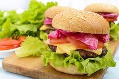 汉堡包用水多的炸肉排、蕃茄、泡菜和黄瓜、乳酪、绿色莴苣叶子和一个软的小圆面包 免版税库存图片