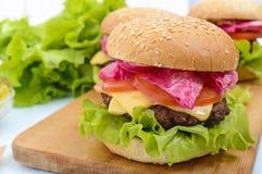 汉堡包用水多的炸肉排、蕃茄、泡菜和黄瓜、乳酪、绿色莴苣叶子和一个软的小圆面包 免版税库存照片