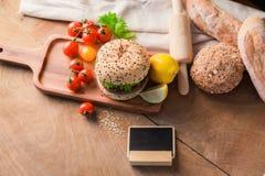 汉堡包自创在木桌上 免版税图库摄影