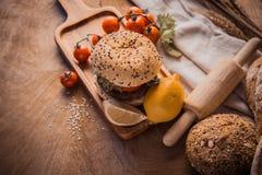 汉堡包自创在木桌上 免版税库存照片