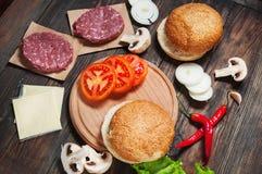 汉堡包自创成份 未加工的剁碎的牛肉,新鲜的小圆面包,切片乳酪,蕃茄,洋葱圈,在木头的莴苣 库存图片