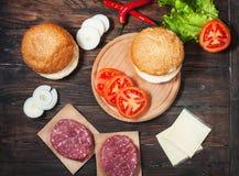 汉堡包自创成份 未加工的剁碎的牛肉,新鲜的小圆面包,切片乳酪,蕃茄,洋葱圈,在木头的莴苣 库存照片
