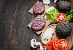 汉堡包自创成份 未加工的剁碎的牛肉,新鲜的黑小圆面包,切片乳酪,蕃茄,洋葱圈,在木头的莴苣 免版税库存照片