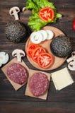 汉堡包自创成份 未加工的剁碎的牛肉,新鲜的黑小圆面包,切片乳酪,蕃茄,洋葱圈,在木头的莴苣 免版税库存图片