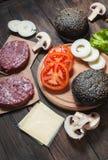 汉堡包自创成份 未加工的剁碎的牛肉,新鲜的黑小圆面包,切片乳酪,蕃茄,洋葱圈,在木背景的莴苣 免版税库存照片