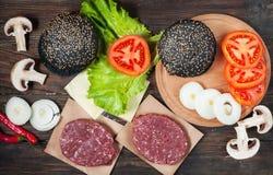 汉堡包自创成份 未加工的剁碎的牛肉,新鲜的黑小圆面包,切片乳酪,蕃茄,洋葱圈,在木背景的莴苣 免版税库存图片