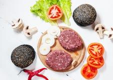 汉堡包自创成份 未加工的剁碎的牛肉,新鲜的黑小圆面包,切片乳酪,蕃茄,洋葱圈,在木白色后面的莴苣 库存照片