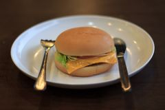 汉堡在一个白色板材精选的焦点,与白色板材的汉堡被安置在桌Blured上或弄脏软的焦点,乳酪汉堡午餐 免版税库存图片