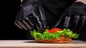 汉堡在黑食物手套的黑背景烹调 非常色情空气小圆面包和使有大理石花纹的牛肉 的餐馆 股票录像
