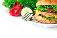 汉堡将面包夹在中间用烟肉、火腿和乳酪与vegetab 免版税库存照片