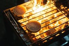 汉堡小圆面包烤与与火的灼烧的木炭在与格栅的火炉在上面在曼谷,泰国 免版税图库摄影
