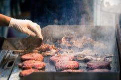汉堡牛肉特写镜头在格栅背景的在开放食物市场上在卢布尔雅那,斯洛文尼亚 免版税库存照片