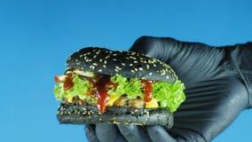 汉堡特写镜头在手中,在一副黑手套的厨师的手展示与一个黑小圆面包莴苣叶子和番茄酱的一个汉堡 股票录像